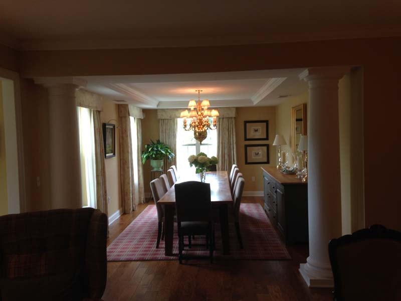 Formal dining room with columns and tray ceiling.